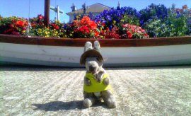 Kanga in front of a boat with floral display